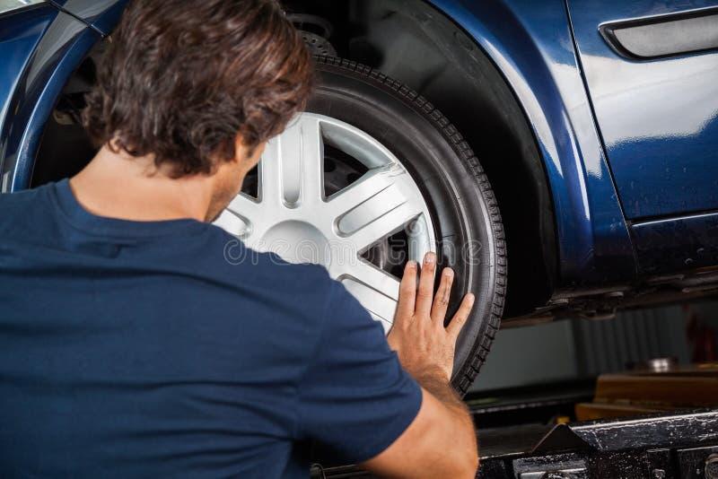 Mechanic Fixing Hubcap To Car Tire. Rear view of male mechanic fixing hubcap to car tire at garage stock photo