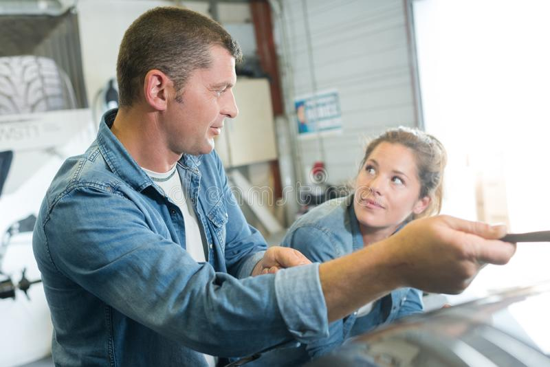 Mechanic giving instructions to female apprentice stock photo