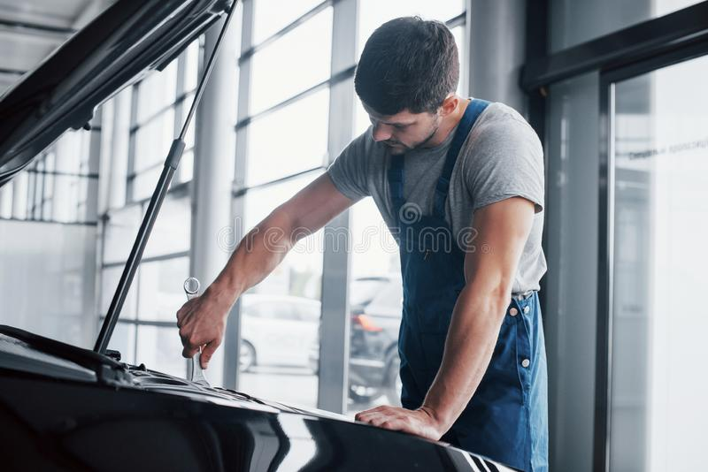 Mechanic hands checking up of serviceability of the car in open hood, close up. royalty free stock photography
