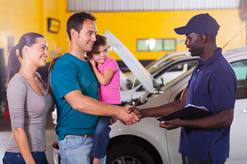 Mechanic handshaking family. Friendly auto mechanic handshaking with family inside workshop royalty free stock photography