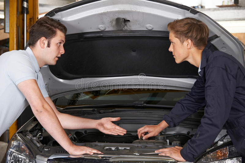Mechanic Helping Apprentice To Fix Engine royalty free stock image