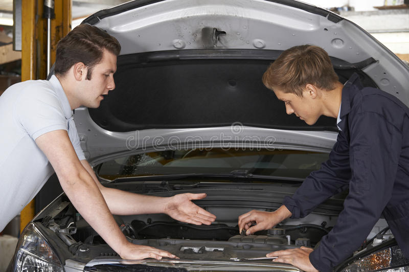 Mechanic Helping Apprentice To Fix Engine stock photos
