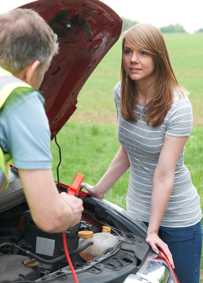 Mechanic Helping Female Motorist With Flat Battery royalty free stock photo
