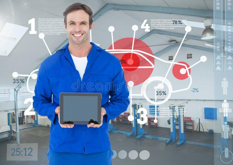 Mechanic holding a digital tablet against digital interface in workshop. Digital composition of mechanic holding a digital tablet against digital interface in stock photos