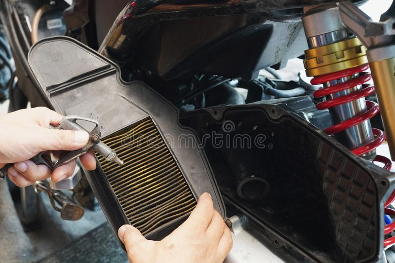 Mechanic holding dirty Engine Air Filter over big scooter and cleaning Filter with air blow gun . maintenance motorcycle concept royalty free stock images