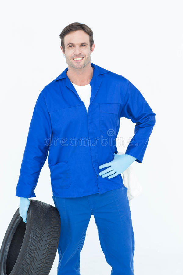 Mechanic holding tire while standing with hand on hip. Portrait of confident mechanic holding tire while standing with hand on hip over white background stock images