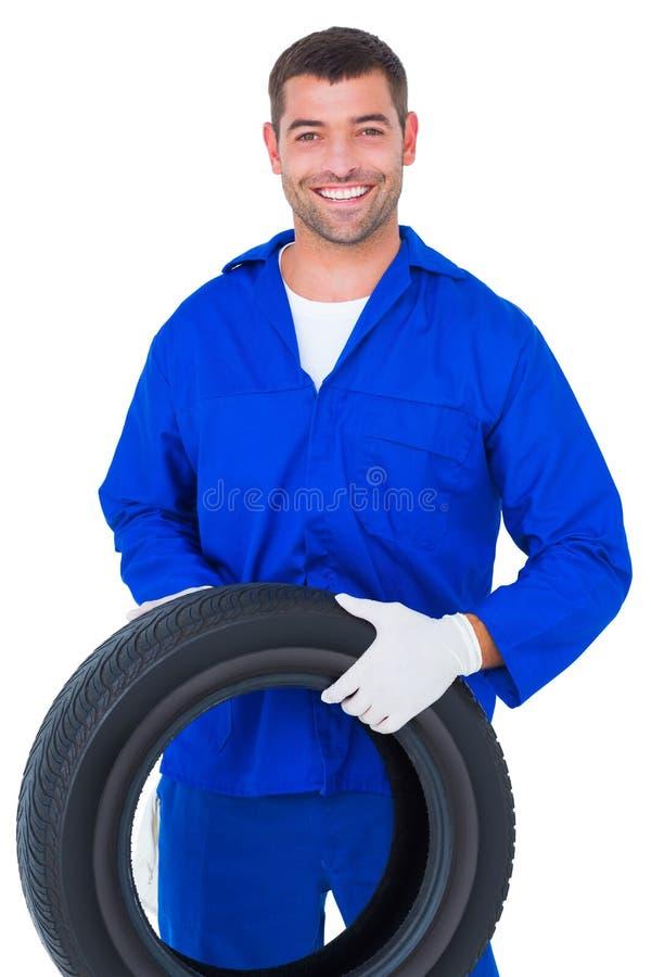 Mechanic holding tire on white background. Portrait of smiling male mechanic holding tire on white background royalty free stock photography