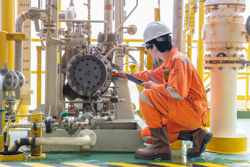 Mechanic inspector engineer check condition of crude oil centrifugal pump and lube oil system at offshore gas platform. Mechanic inspector engineer check royalty free stock image