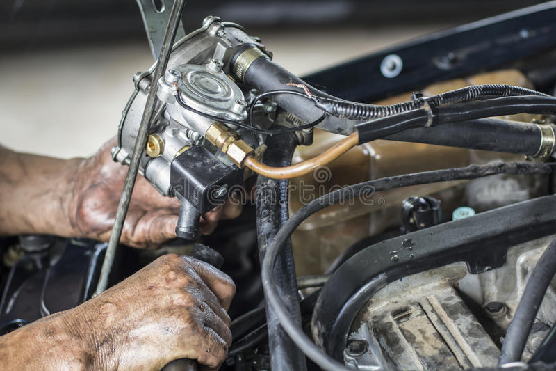 Mechanic install new car gas vaporizer in old car. Bi-fuel alternative royalty free stock photography