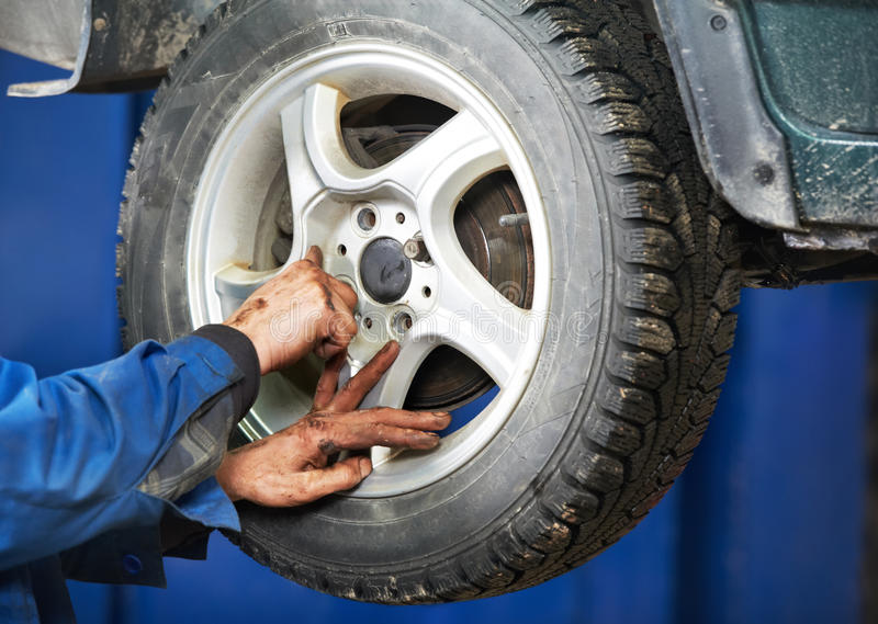 Mechanic installing car wheel at service station. Mechanic technician worker installing car wheel at maintenance and repair auto service station royalty free stock photo