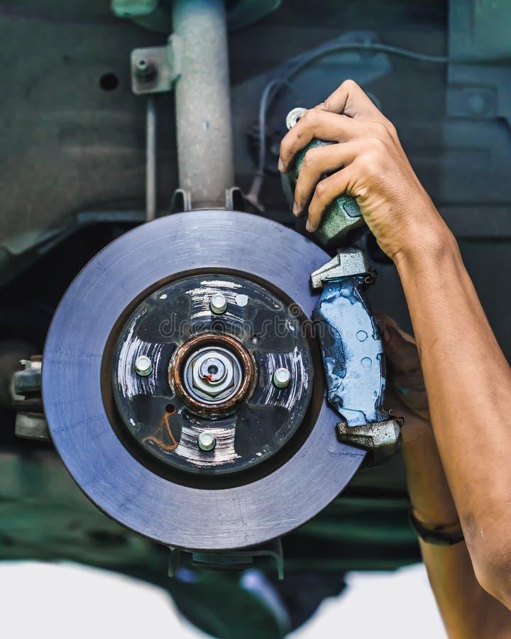A mechanic installs brake lining onto a car disc brake. Hands of a mechanic install brake lining onto a car disc brake royalty free stock photo