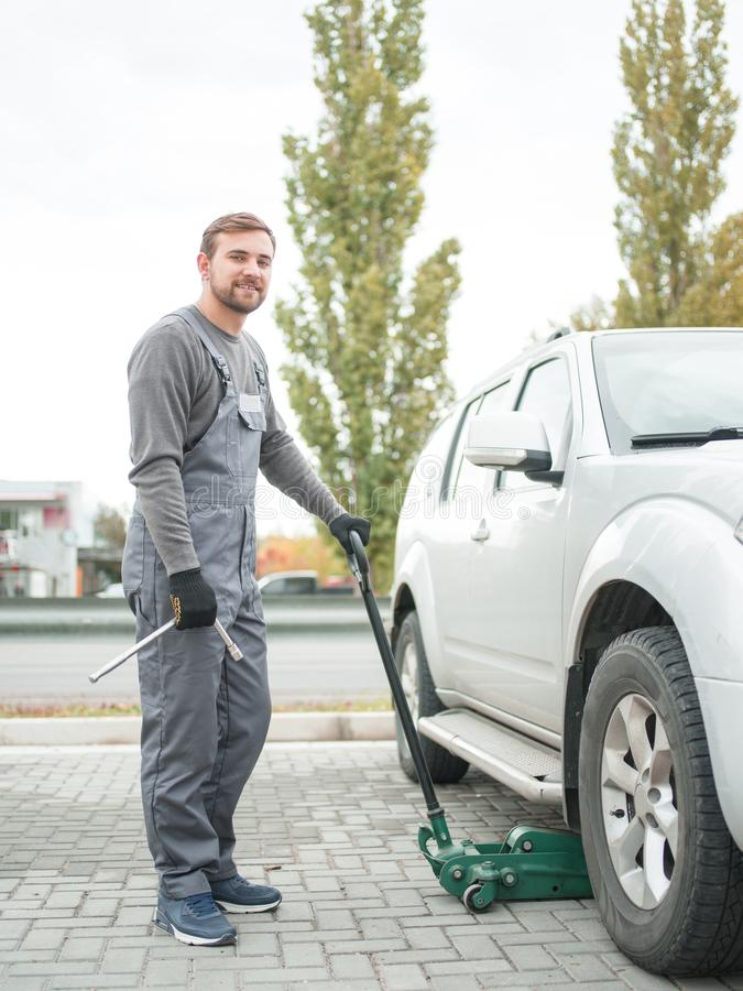 The mechanic lifts the car with a jack outdoors. royalty free stock images