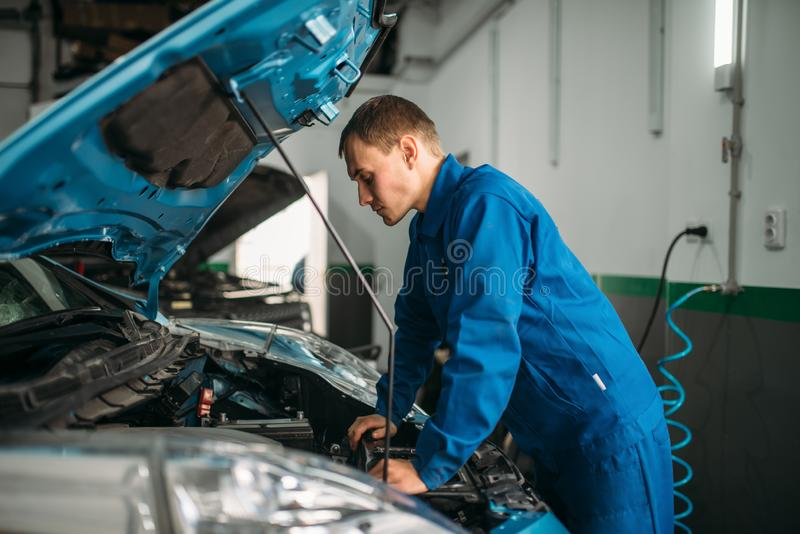 Mechanic makes visual inspection of the car engine. Motor diagnostic. Car with opened hood, auto-service royalty free stock photography