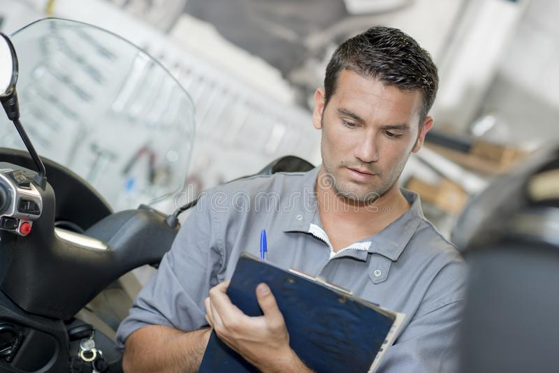 Mechanic making notes on clipboard stock images