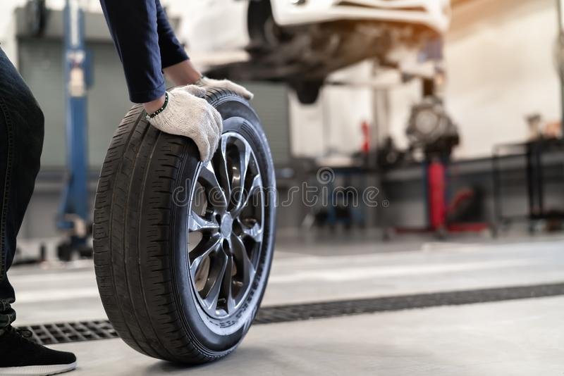Mechanic man change a wheel tire and service maintenance the suspension of a vehicle royalty free stock images