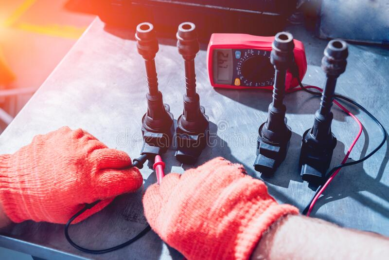 Mechanic man with digital multimeter testing ignition coil stock photography