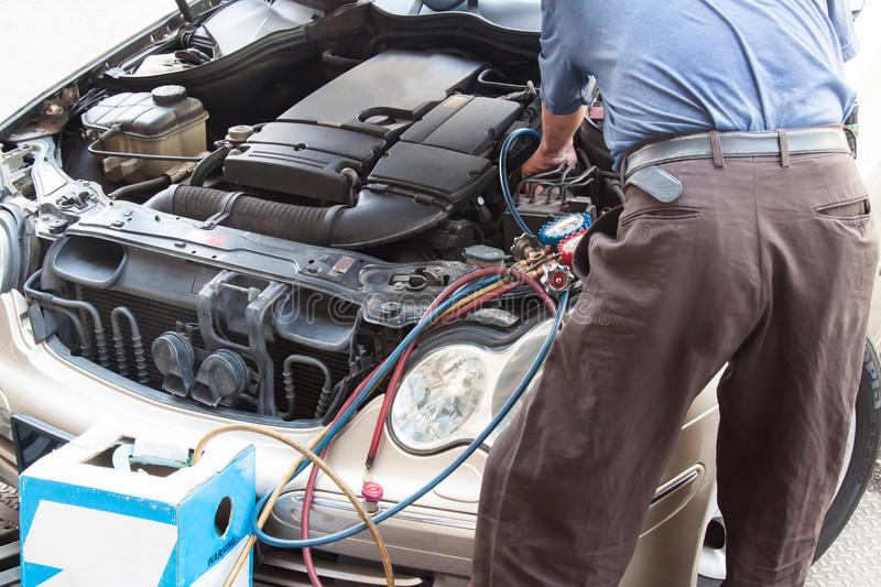 Mechanic with manometer filling gas into auto vehicle air-condit. Ion compresser stock photography