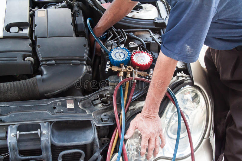 Mechanic with manometer inspecting auto vehicle air-condition co. Mpresser with manometer royalty free stock photo