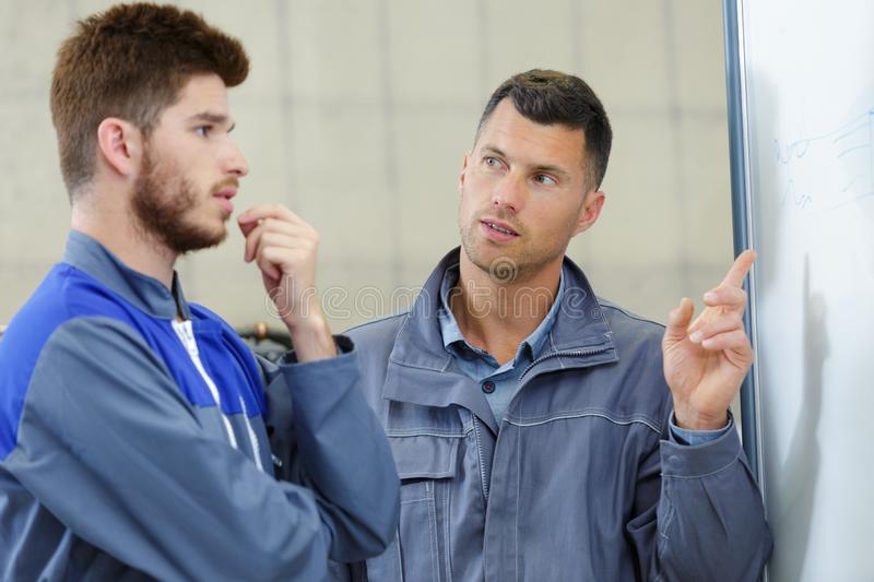 2 mechanic men looking at problem stock image