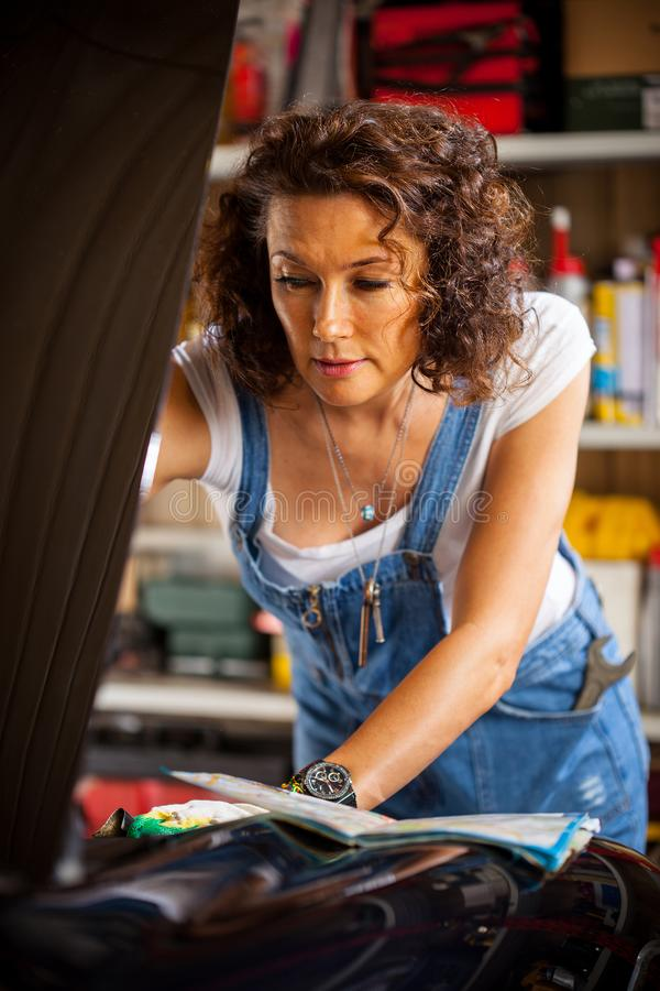 Mechanic woman in a blue coveralls adjusts the car`s engine royalty free stock image