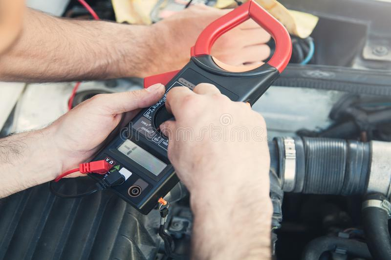 Mechanic with a multimeter testing car engine. Car service stock images