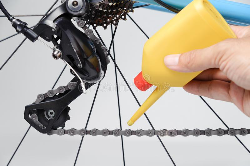Mechanic oiling bicycle chain and gear with oil. Close up of bicycle components royalty free stock photography