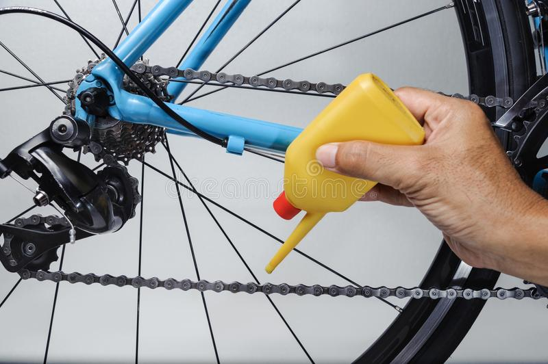 Mechanic oiling bicycle chain and gear with oil. Studio shot royalty free stock photo