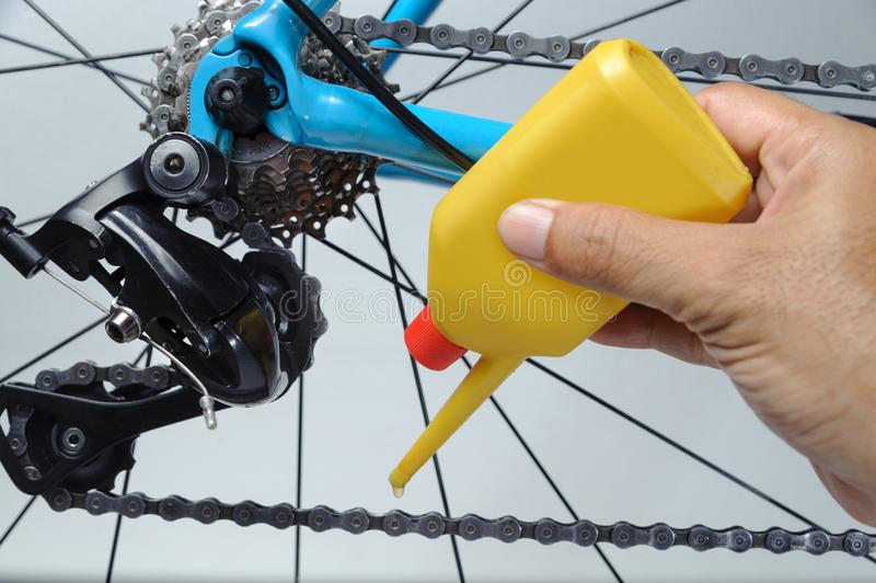 Mechanic oiling bicycle chain and gear with oil. Studio shot stock image