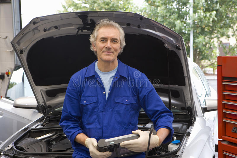 Mechanic by open bonnet of car, portrait royalty free stock images