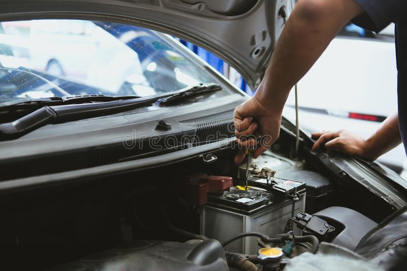 Mechanic opening closing checking car battery in automobile repair service. Garage royalty free stock photos