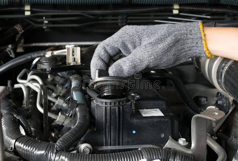 A mechanic is opening the oil cap from a car engine. royalty free stock image