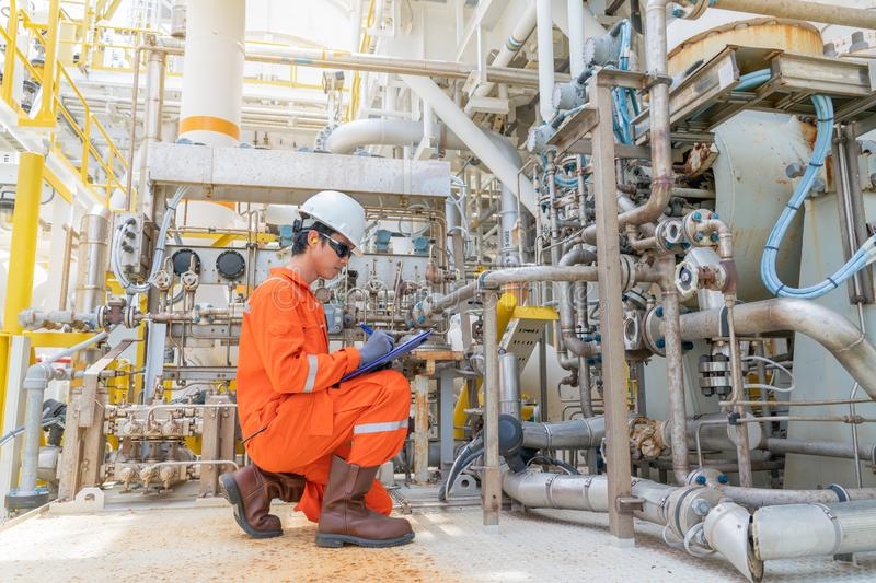 Mechanic operator check lube oil and seal gas systems of gases compressor on offshore central processing platform.  stock image