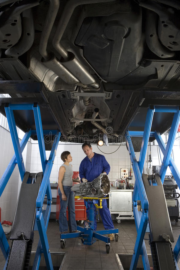 Mechanic with part in conversation with woman by elevated car, low angle view. Mechanic with part in conversation with women by elevated car, low angle view stock photo