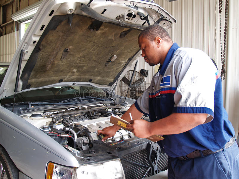 Mechanic Performing a Routine Service Inspection. Auto mechanic checking radiator levels while performing a routine service inspection in a service garage stock images