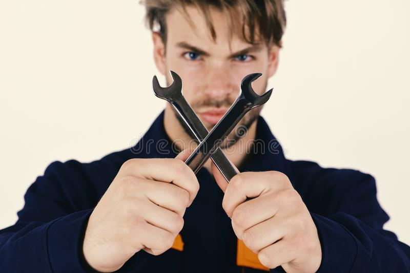 Mechanic or plumber with spanners in hands. Spanner instrument for fixing or tightening details. royalty free stock photography