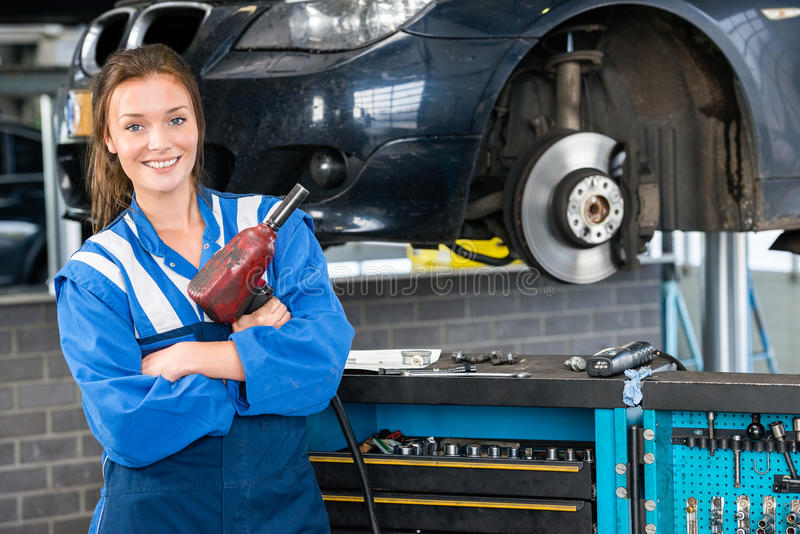Mechanic With Pneumatic Wrench Standing By Car royalty free stock photo