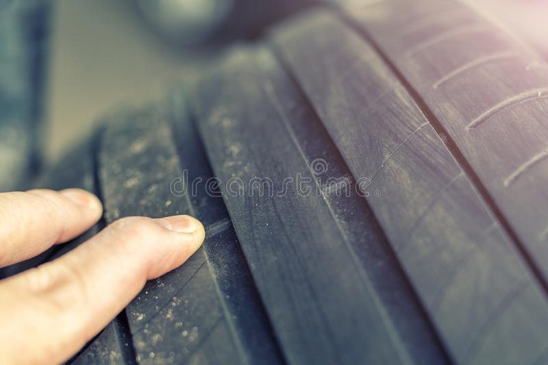 Mechanic pointing with hand at tyre wear indicator at car service center. Vehicle wheel protector control and inspection during stock photography