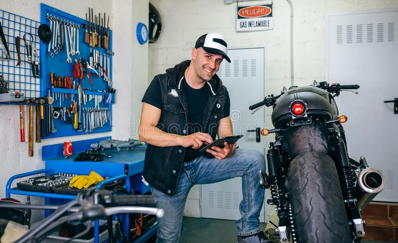 Mechanic checking custom motorcycle with tablet. Mechanic posing checking custom motorcycle with tablet in his workshop stock photography