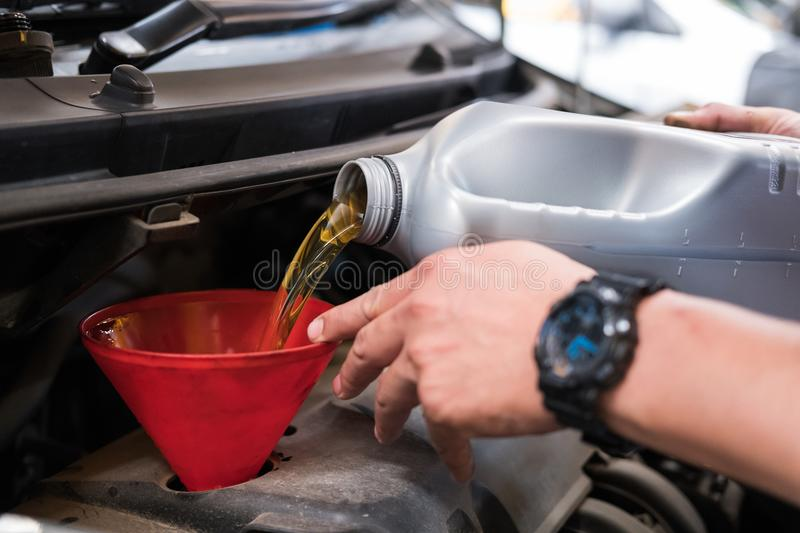 mechanic pouring oil to vehicle engine. serviceman changing motor oil in automobile repair service. maintenance & checkup in car stock images