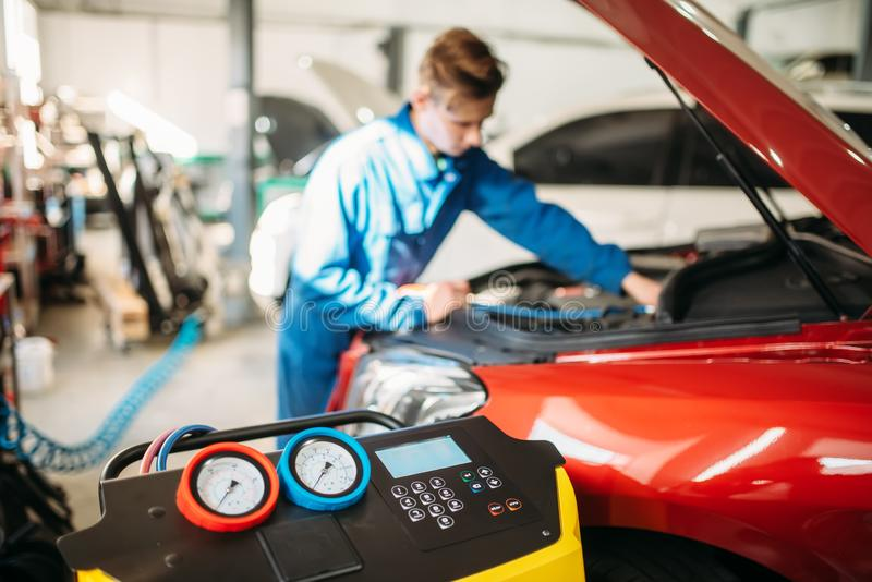 Mechanic pumps freon into the conditioning system. Mechanic pumps freon into the car air conditioning system. Conditioner inspection in auto-service stock photography