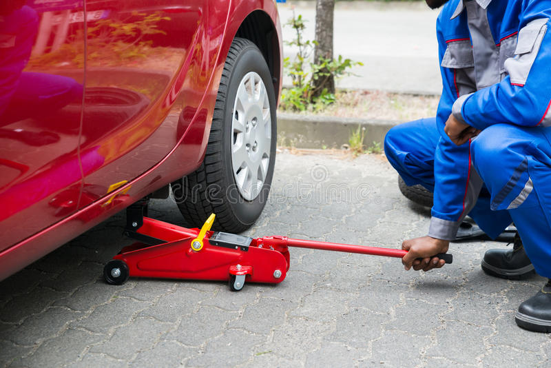 Mechanic Putting Hydraulic Floor Jack Inside The Car. Young Male Mechanic Putting Red Hydraulic Floor Jack Inside The Car royalty free stock image