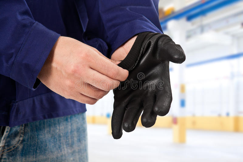 Mechanic putting safety gloves royalty free stock photography