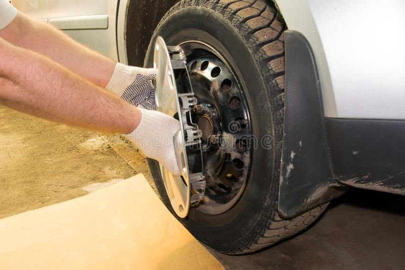 A mechanic removing the hubcap from a car wheel. Tire fitting stock images