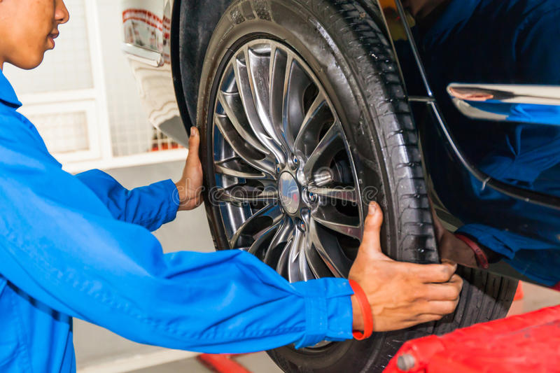 Mechanic removing or replacing car wheel at car service garage royalty free stock photos