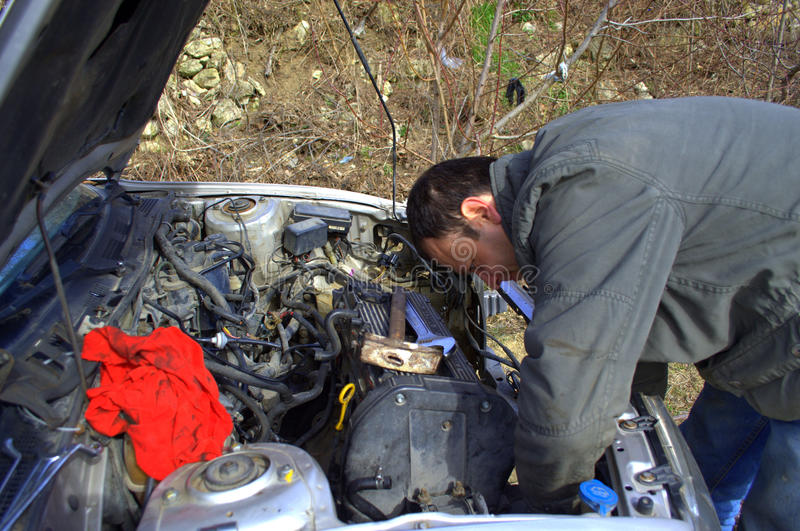 Mechanic repair car. Mechanic repairman working under the hood of an old automobile car engine royalty free stock photo