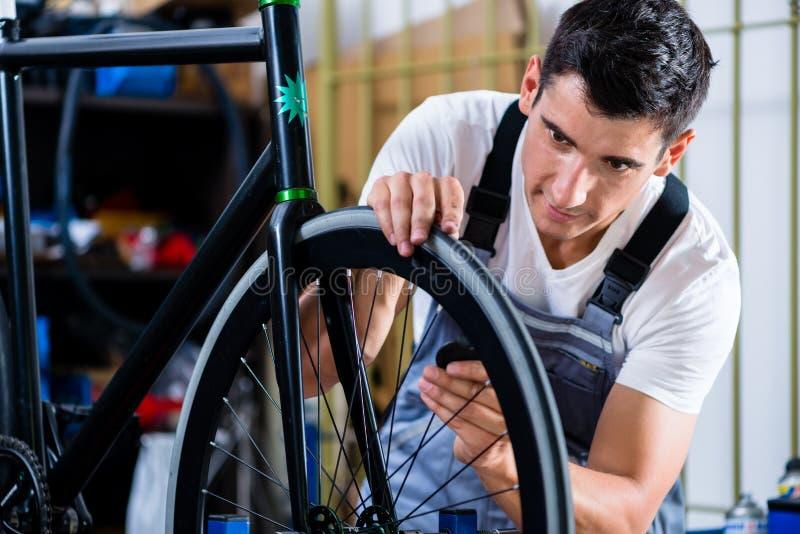 Mechanic repairing bicycle in his workshop stock photos