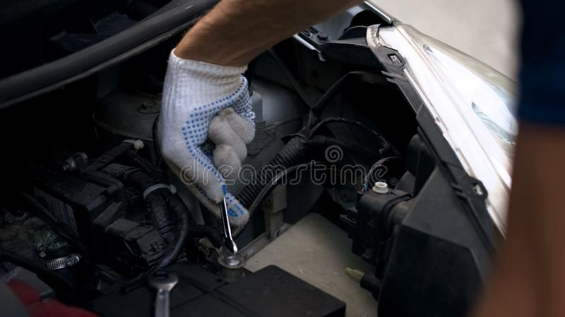 Mechanic repairing car engine, fixing automotive battery, breakage under hood royalty free stock images