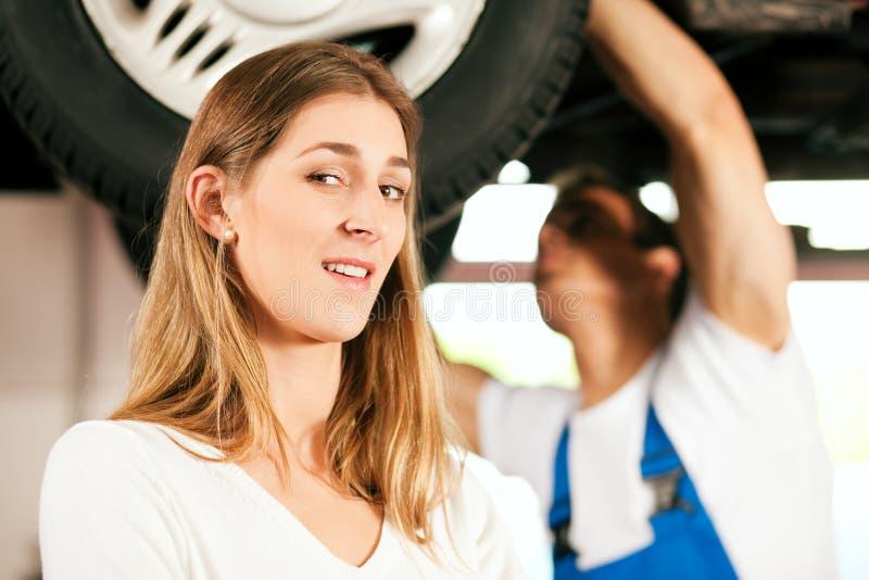 Mechanic repairing car of woman royalty free stock images