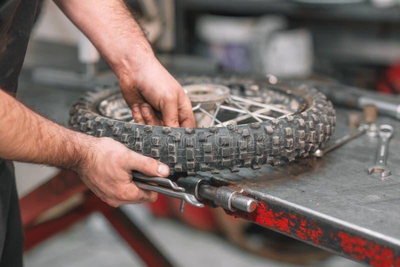Mechanic repairing damaged motorcycle tire, in repair shop. Mechanic repairing damaged motorcycle tire, in repair shop royalty free stock photography