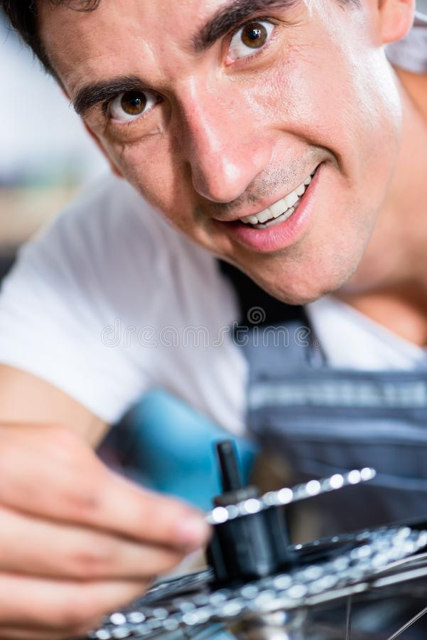 Mechanic repairing gears of bicycle. In workshop stock image